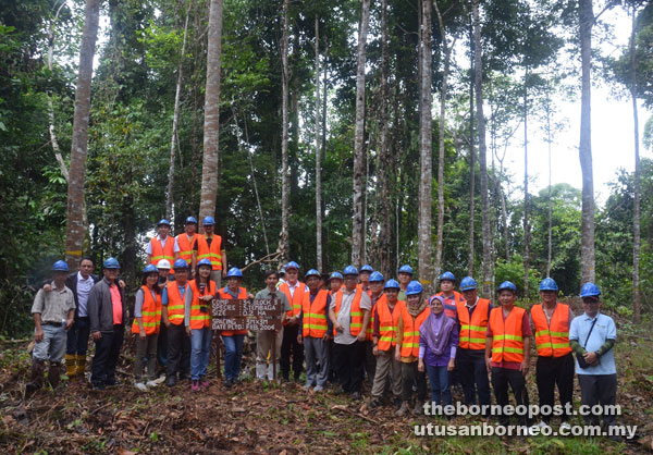 Visitors in a group photo taken after a field visit to the tree planting area.
